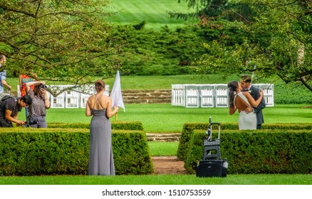 LISLE, IL/USA - SEPT. 21, 2019: Bride and groom kiss while a wedding photographer takes pictures, a videographer captures footage, and a bridesmaid watches, holding an umbrella, at Morton Arboretum.