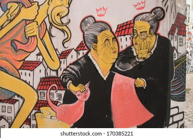 Lissabon, Portugal, November 1, 2013:Anonymous graffiti image shows the talking portuguese grandmother concerning with knitting. Graffiti is located in old city.