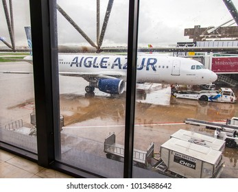 LISSABON, PORTUGAL, on January 5, 2018. A view through a wet window of the airport of the airfield and planes