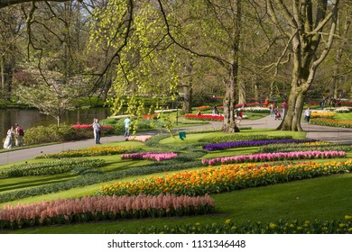 Lisse, Netherlands - April 19, 2018:  Colored flower beds in the keukenhof park with tourists in the background