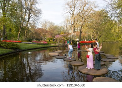 Lisse, Netherlands - April 19, 2018: Tourists take pictures, from stone tiles in the water of the flowers in the park
