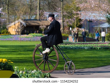 LISSE, NETHERLANDS - APRIL 2, 2017: Unknown man in old-fashoned clothing riding a 19th century velocipede