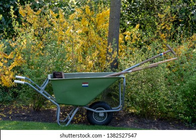 Lisse, Netherlands. April 2019. Green wheelbarrow with gardening tools inside, photographed at Keukenhof Gardens, Lisse, South Holland. Lisse is the centre of Holland's floriculture industry.