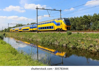 LISSE, NETHERLANDS - AUGUST 9, 2015: Dutch yellow and blue train reflected in a canal
