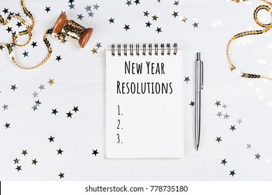 List of new year resolutions in beautiful note pad. Festive background with stars.