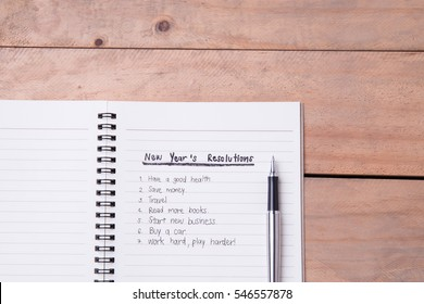 List of New Year's resolution on notepad, vintage style on wood with space for layout.