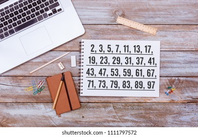 List of Prime Numbers below 100, text written on paper note pad, grunge wood table flat lay shot from above