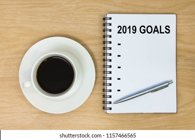 List year 2019 goals on paper wood table background. New Year's Resolution on book and hot coffee cup. Target success concept.  top view.