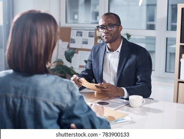 Listen attentively. Skillful young pleasant businessman in suit is sitting at table and holding papers while looking at responsible colleague female who sitting in front of him