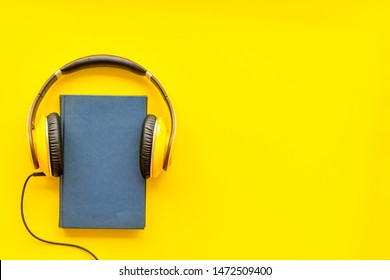 listen to audio books with headphone on yellow background flatlay mock up