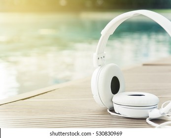 Listen to music concept. White earphones on wooden background near  swimming pool with summer sunlight. Selective focus.