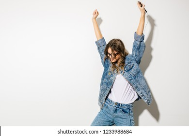 listen to the music and dance. concept with a young expressive beautiful woman in retro jeans outfit listening music with headphones and dancing, on white background