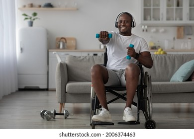 Listen to music while exercising at home, workout to recover and keep fit, enjoying audio app. Disabled adult man in wheelchair with headphones lifts up dumbbells in living room interior, empty space