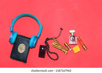 listen to quran concept, holy muslim book and bluetooth headphone and rosary, siwak, perfume  isolated on red background