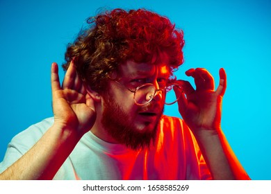 Listen to secrets, attented. Caucasian man's portrait isolated on blue studio background in neon light. Beautiful male model, red curly hair. Concept of human emotions, facial expression, sales, ad.
