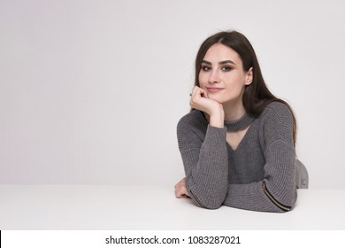 I listen to you carefully. Beautiful brunette girl sitting at table on gray background and smiling. She sits right in front of the camera and looks happy