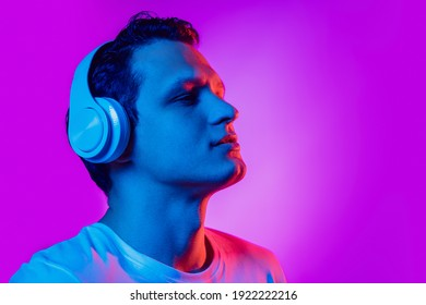 Listening to music. Caucasian man's portrait on purple studio background in multicolored neon light. Beautiful male model. Concept of human emotions, facial expression, sales, ad, fashion. Copyspace.