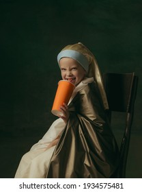 Listening to music with headphones, drinking cocktail. Medieval little girl as lady with a pearl earring on dark studio background. Concept of comparison of eras, childhood, ancient. Stylish, creative