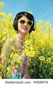 listening music on a field of spring canola flowers.