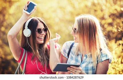 Listening to music. Two smiling girls walking through the city park and enjoying in music. Lifestyle concept