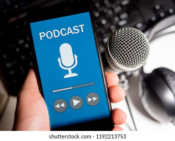 Listening podcast in phone with microphone, headphones and keyboard on white desktop. First person point of view