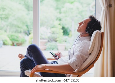 listening relaxing music at home, relaxed man in headphones sitting in deck chair in modern bright interior