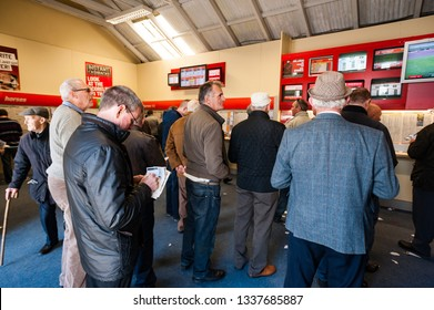 Listowel - September 20 2014: People watching live horse racing at a bookies centre in the republic of Ireland