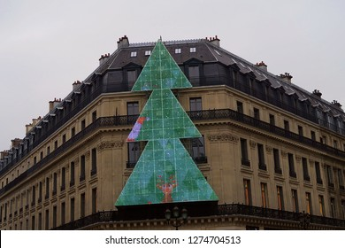 Lit and animated Christmas tree in Paris. Large tree hung from building side.