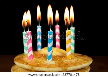 lit birthday candles on stack pancakes stock photo edit now