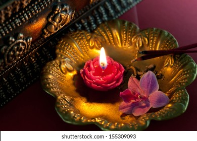 Lit candle and burning incenses