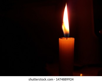 Lit candle in a dark room.