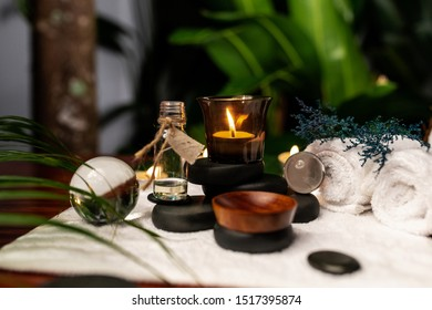 A lit candle and a jar of aromatic oils standing on stones for stone therapy and located on a towel next to which are transparent spheres, a twisted terry towel of white color and a sprig of lavender