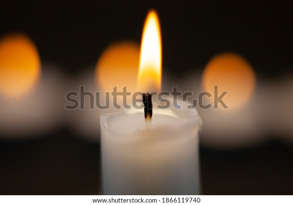 A lit candle on a black background with a slightly hazy background