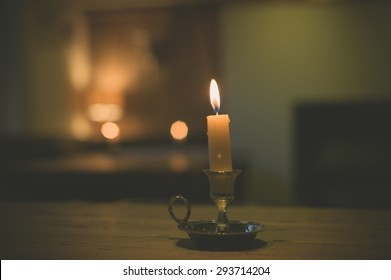 A lit candle on a table in a dining room