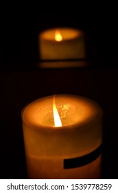 Lit candle with reflection in dark room