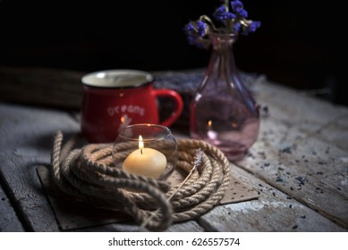 Lit candle, rope, red Cup, pink vase with flower