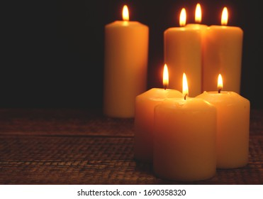 Lit candle stands against dark background