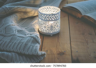 Lit Candle White Knitted Sweater Open Book on Plank Wood Table by Window. Cozy Winter Autumn Evening. Natural Light Authentic Tranquil Atmosphere. Kinfolk Hygge Slow Living Style. Matte Toned