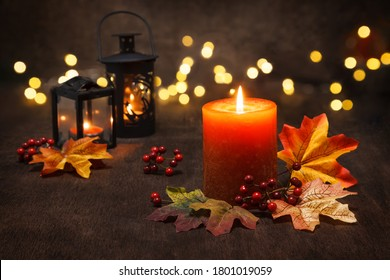Lit candles with  autumn leaves and fall decoration.