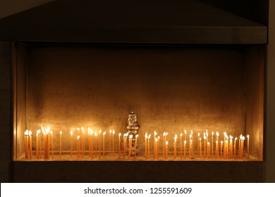 Lit candles candle light a small lamp kept permanently burning placed on sand in a church of a Greek monastery in darkness in Greece