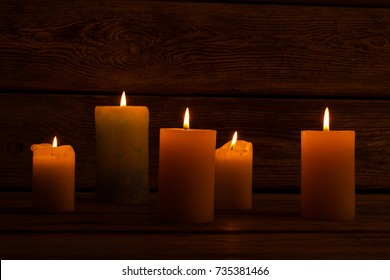 Lit candles in dark room. Warm candlelight to create cozy and festive ambiance. Home decoration for winter holidays.