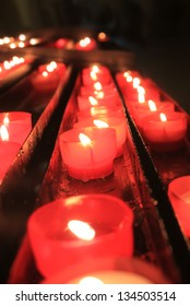 Lit candles in small red holders in a row, each one lit for a prayer in a church in Portugal