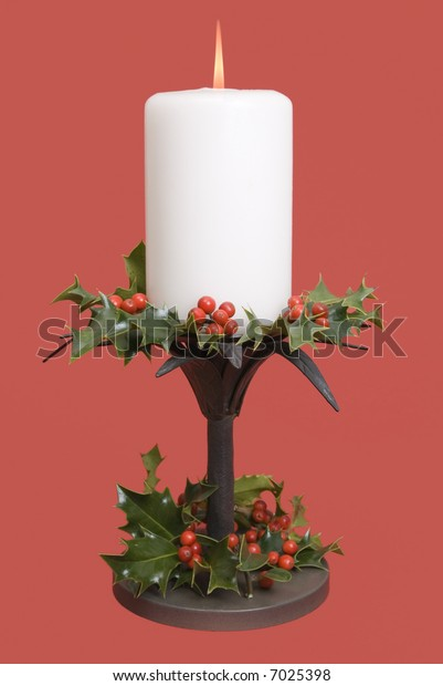 Lit Christmas candle on red festive background with holly and berries