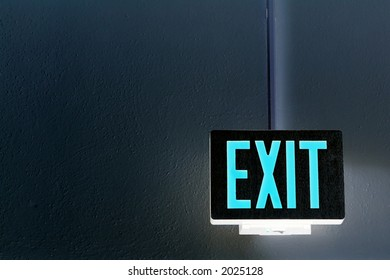 lit exit sign hanging from the ceiling