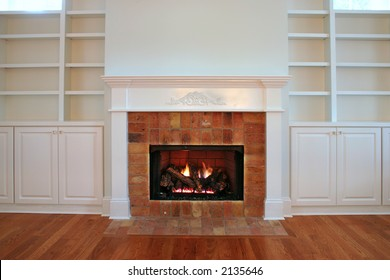 lit fireplace surrounded by built in bookshelves.