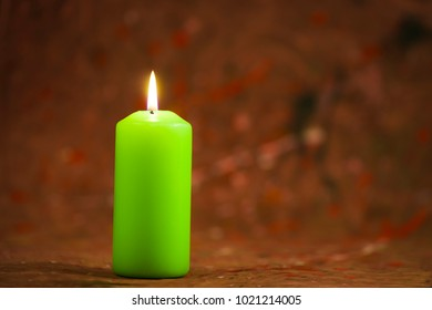 Lit green candle on a fuzzy abstract image background
