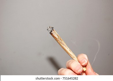 Lit joint being held up against a plain background