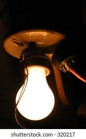 Lit Light Bulb in a Dark Garage