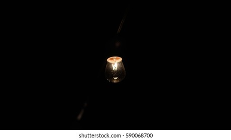 A lit lightbulb surrounded by darkness.