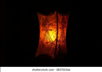 Lit Moroccan lamp on black background. Handmade traditional henna lamp from Morocco. Tattooed henna designs and symbols on lit leather lamp.